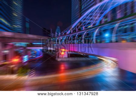Light trails from the vehicles at the intersection with a walk-over pedestrain bridge