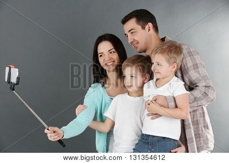 Happy family making selfie with selfie stick on grey background
