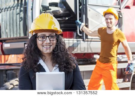 Young Female Engineer Posing In Junkyard With A Worker