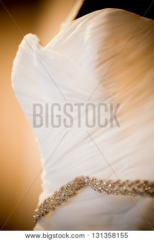 Wedding dress top close up in warm light.