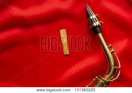 wooden Reeds and saxophone mouthpiece on a red background