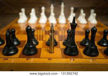 Big riffle bullet in row of chess pieces. Concept of weapon power