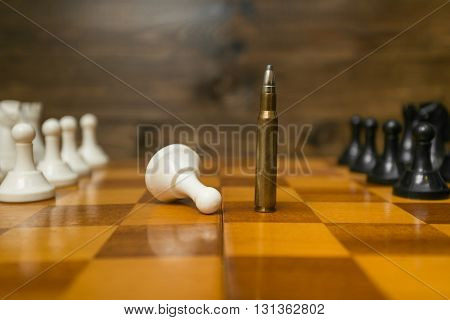 Conceptual photo of riffle bullet on chessboard. Concept of power of guns