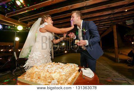 Funny portrait of bride feeding groom with wedding cake at restaurant