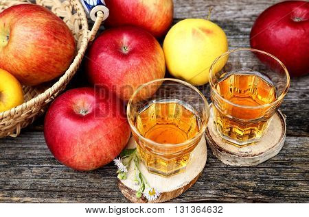 Apple juice in two glass on old wooden table and many apples