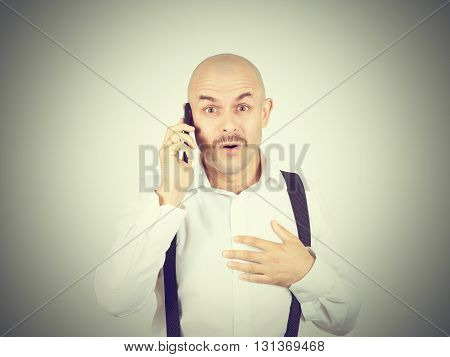 Bald Mustachioed Man Talking On The Phone.