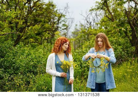 Best friends forever. Girlfriends collect wildflowers. BFF. Walk. She weaves a wreath of flowers.