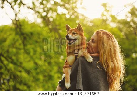 Girl and dog Shiba Inu hug in a spring park. Walking with a pet. Pedigree dog. Walking dogs. Dog happiness.