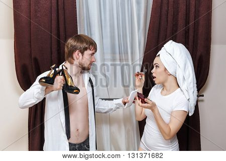 Morning couples. Husband and wife are going to work. The man brought her shoes. Girl doing make-up with a towel on her head.