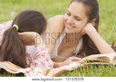 smiling mother and daughter lying on the plaid and lookin at each other