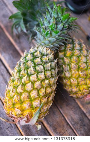 Two small ripe sweet pineapples on wood background