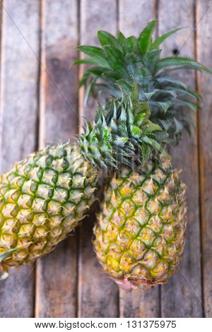 Two ripe sweet pineapples on wood background