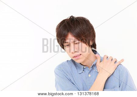 studio shot of young Japanese man suffers from neck ache on white background