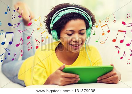 people, technology and leisure concept - happy african american young woman lying on sofa with tablet pc computer and headphones listening to music at home over notes background