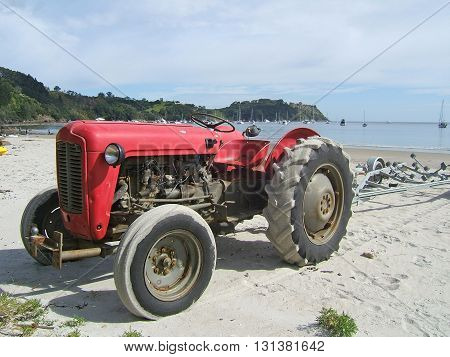 Old red tractor on a beach, ready for recovering a fishing boat from the sea. Photographed at Whitianga, Coromandel Peninsula, New Zealand.