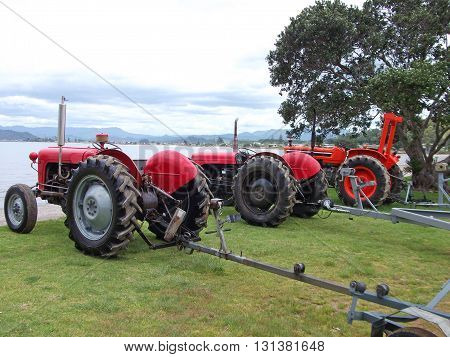 A row of old red tractors on a beach, ready for recovering fishing boats from the sea. Photographed at Whitianga, Coromandel Peninsula, New Zealand.