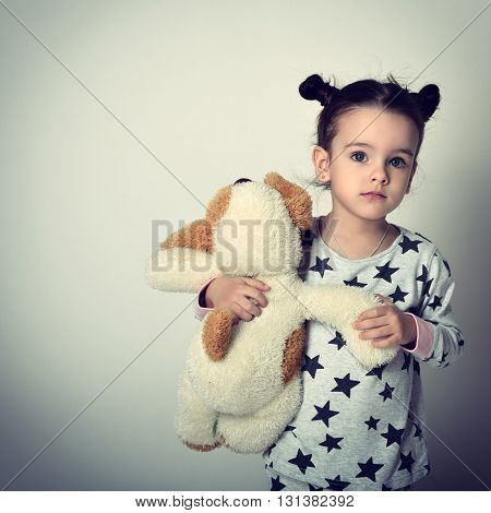 Little lovely sleepless girl in pajamas holding her loved plush toy. Insomnia. Children's fears.