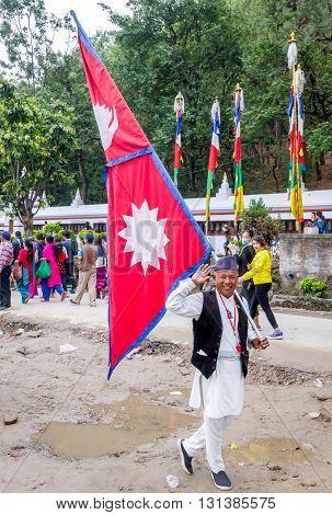 KathmanduNepal - May 21 2016 : An old man with the flag of Nepal in Nepali national dress in swayambhunath on Buddha's Birthday.Prayers are walking to round the Swayambhunath Stupa at the back.