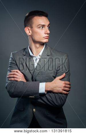 Serious businessman standing with arms folded over gray background and looking away