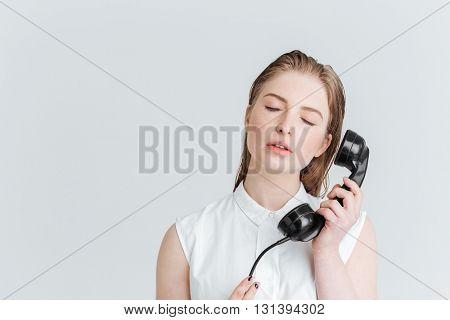 Relaxed woman with closed eyes holding retro phone tube isolated on a white background