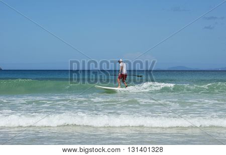 Paddleboarder on a SUP surfing a wave. Paddle boarder photographed in Northland, New Zealand.