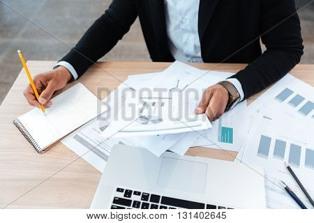 Close-up portrait of hands holding documents and making notes in the office