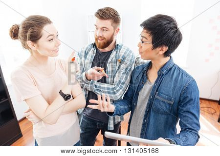Cheerful young businesspeople standing and discussing bisness plan using tablet in office
