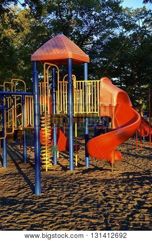 The early morning sun rays shine upon a children's playground in a park