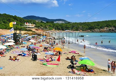 SANTA EULALIA, SPAIN - JUNE 14: Sunbathers in Cala Nova Beach on June 14, 2015, in Santa Eulalia Del Rio, Ibiza, Balearic Islands, Spain. Ibiza is a well-known summer tourist destination in Europe