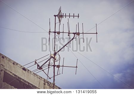Vintage look filter, Old antenna with blue sky background. Silhouetted image (antenna, television, silhouetted)