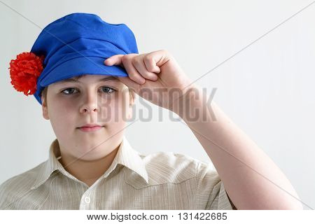 Portrait of a boy teenager in Russian national cap with cloves