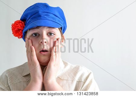 Portrait of the surprised boy teenager in Russian national cap with cloves