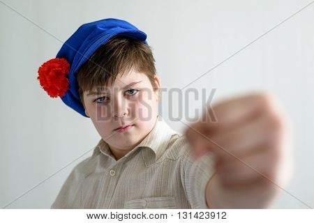 a boy teenager in Russian national cap with cloves showing a fist