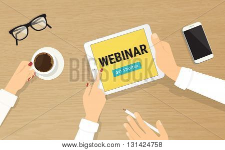 Human hands hold a tablet pc with webinar invitation on the display and showing it to his colleague. Top view of realistic wooden table on the office with grasses, smartphone and coffee cup