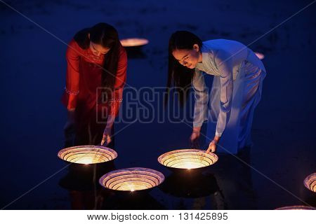 Women dressed in traditional Vietnamese are Lamplighter in river.