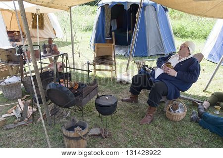 Tewkesbury, UK-July 17, 2015: Historical Reenactor awaits lunch in the Living History Camp on 17 July 2015 at Tewkesbury Medieval Festival