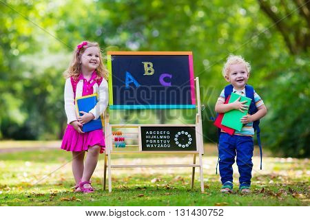 Children happy to be back to school. Preschooler girl and boy with backpack and books at black chalk board learning to write letters and read. Kids at preschool or kindergarten learn the alphabet.