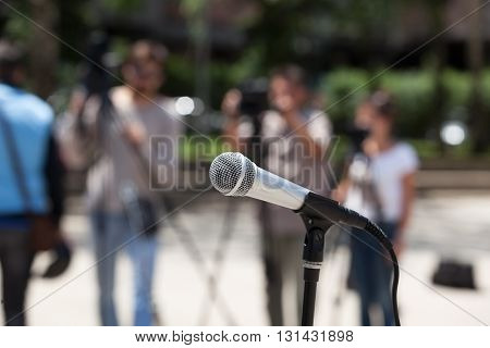 Microphone in focus against blurred journalists and camerman