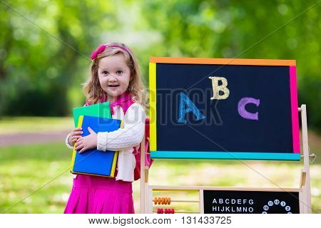 Child happy to be back to school. Funny little preschooler girl with backpack and books at black chalk board learning to write letters and read. Kids at preschool or kindergarten learn the alphabet.