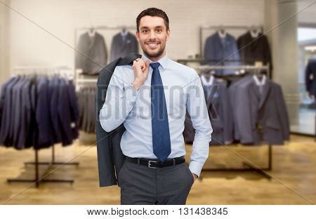 business, people, menswear, sale and clothes concept - happy young businessman over clothing store background