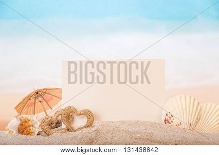Blank white card with sea shells and hearts in the sand on the beach.