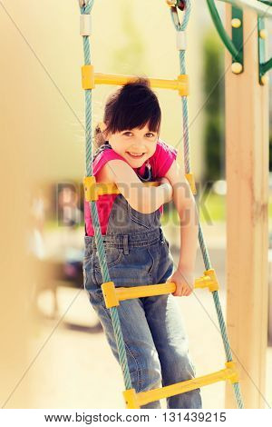 summer, childhood, leisure and people concept - happy little girl on children playground climbing by rope-ladder