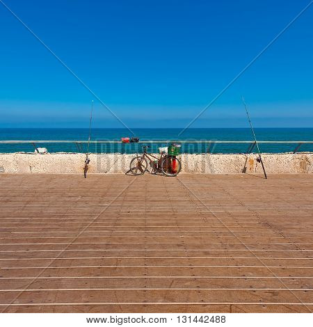 Bicycle and Fishing Rod on the Promenade of the Old Port in Tel Aviv
