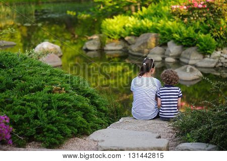 Woman with her son on the bank of the pond. They sit huddled together on the big gray boulder. The calm water of the pond reflected scenic shore. Boy and woman admiring the scenery. Peace and harmony