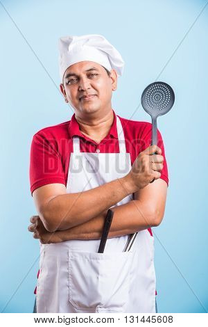 indian male Chef Holding spoon skimmer Isolated On blue Background, asian male chef holding spoon