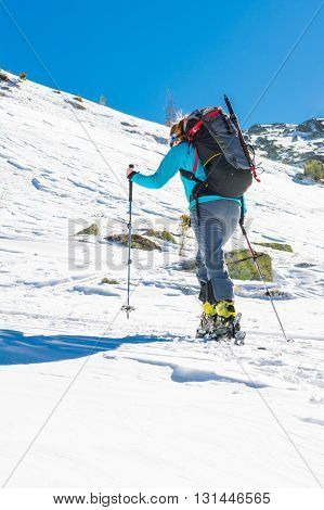 Skier ascending a slope. Ski touring where skier is tackling a steep slope. poster