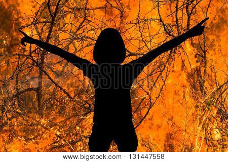 Silhouette of woman with arms raised in the flames. Concept of danger, of strength, of courage, of heroism, of devil.