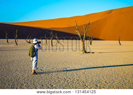 Travel to Namibia. Namib-Naukluft National Park. The dried-up lake surrounded by orange dunes. Elderly woman - tourist photographing picturesque dried tree