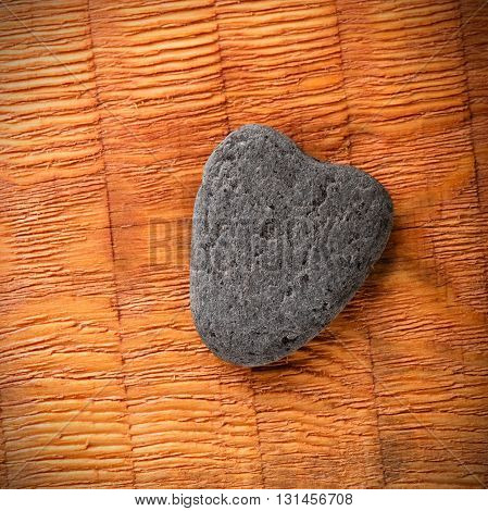 Square photo of slate grey stone with shape of heart. Heart shaped stone placed on wooden board with parallel grooves. Corners with visible vignetting.