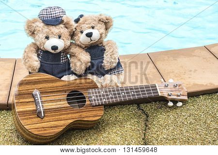 two teddy bear holding hand with ukulele and sitting on pool background love and friendship concept